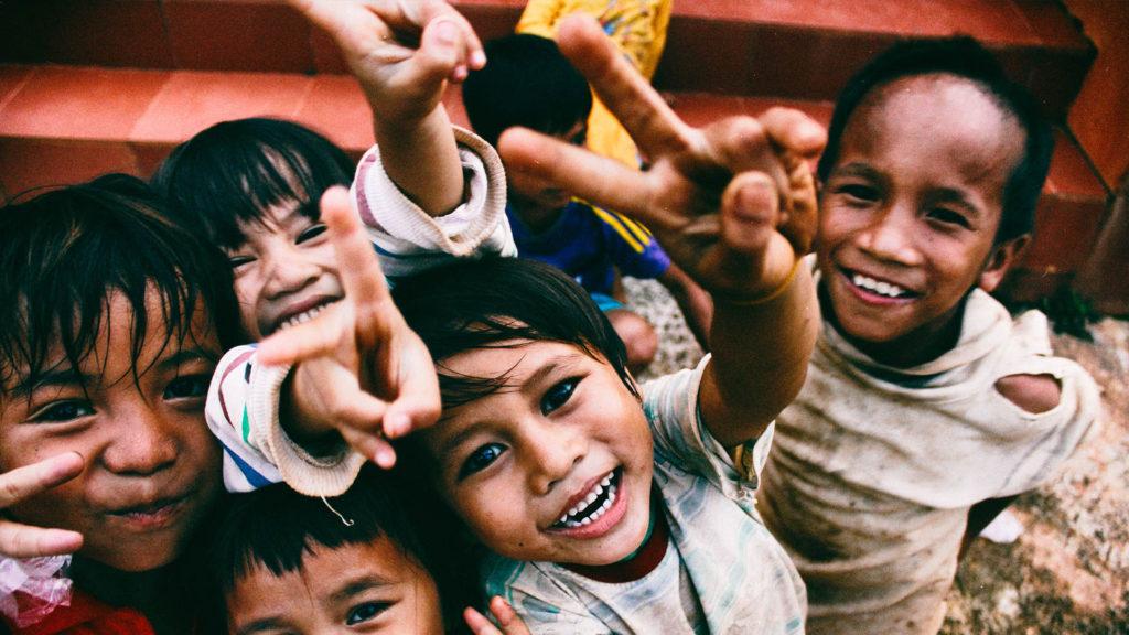 Eine Gruppe von Kindern hält einem Finger mit Peace Zeichen entgegen